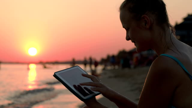 Happy woman with pad on beach at sunset video