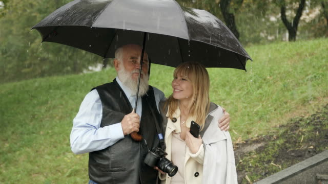 Happy woman with senior man walks during the rain in park, marriage by prexy video