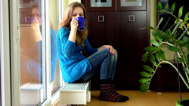 Happy Woman With Warm Clothes Drink Tea And Dream Sitting On