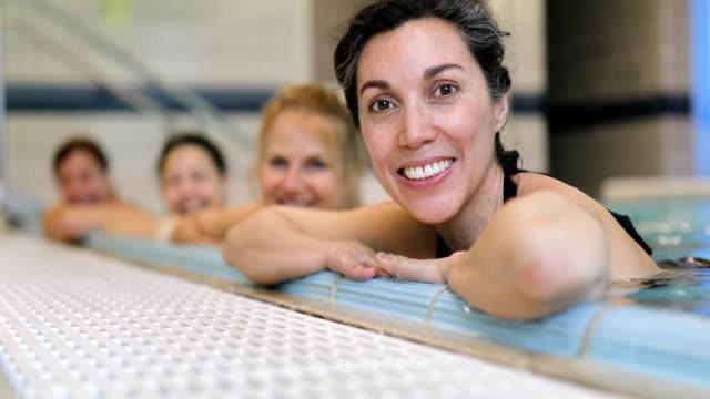 happy women leaning on poolside at health club - 40 49 lat filmów i materiałów b-roll
