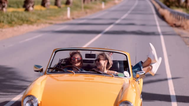 happy women on road trip driving vintage yellow cabriolet car - road trip стоковые видео и кадры b-roll