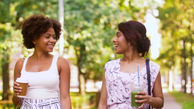 happy women or friends walking along summer park