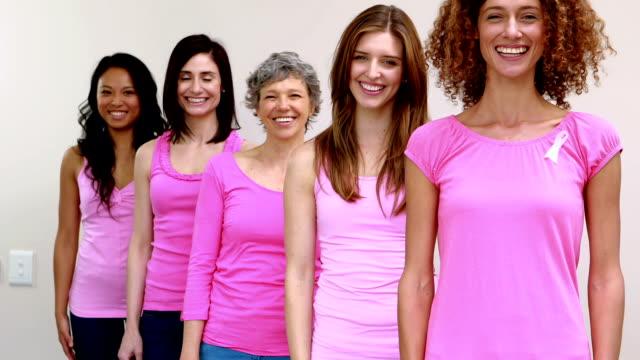 szczęśliwy kobiet stojący w wierszu - breast cancer awareness filmów i materiałów b-roll
