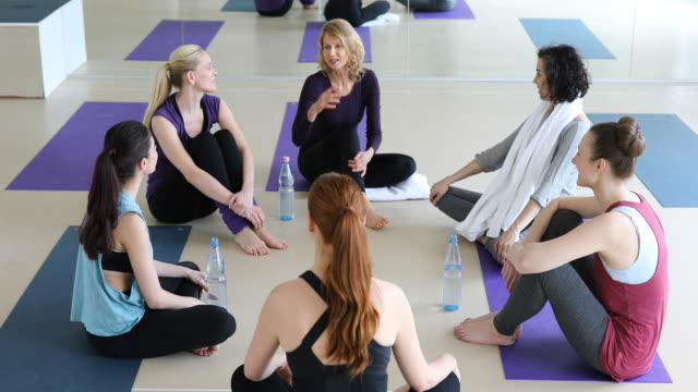 Happy women talking while sitting at yoga class video