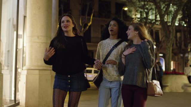 glückliche frauen sprechen während des gehens in stadt bei nacht - schaufenster stock-videos und b-roll-filmmaterial