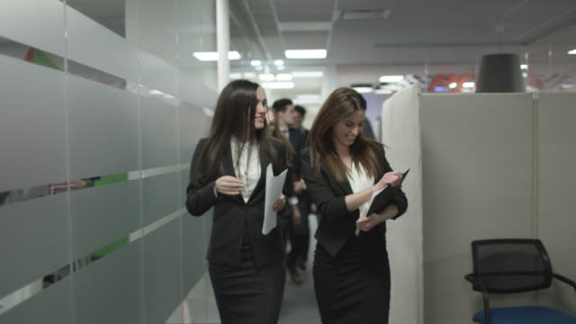 happy women walking through the office building - служащая стоковые видео и кадры b-roll