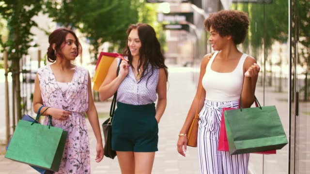 happy women with shopping bags walking in city sale, consumerism and people concept - happy young women with shopping bags walking along city street buying stock videos & royalty-free footage