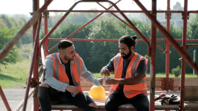 vídeos de stock e filmes b-roll de happy workers in construction site during lunch break - sanduíche
