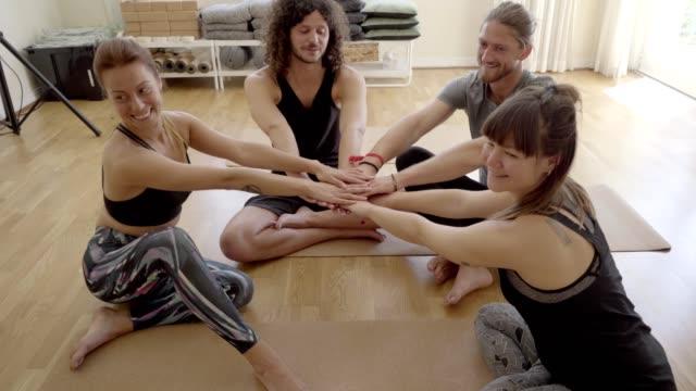 ハッピーヨガグループは、屋内で手を積み重ねる - スポーツ用品点の映像素材/bロール