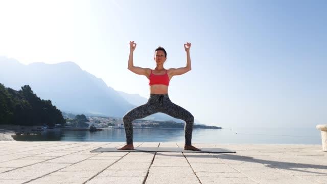 Happy yoga woman meditating in calm seascape