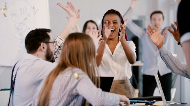 Happy young African American female boss celebrating success with multiethnic team, confetti falling at office meeting. video