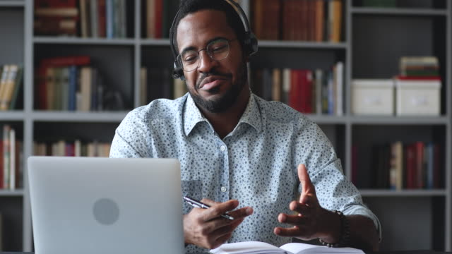 vidéos et rushes de jeune homme afro-américain heureux retenant l'appel vidéo avec l'entraîneur. - vidéoconférence
