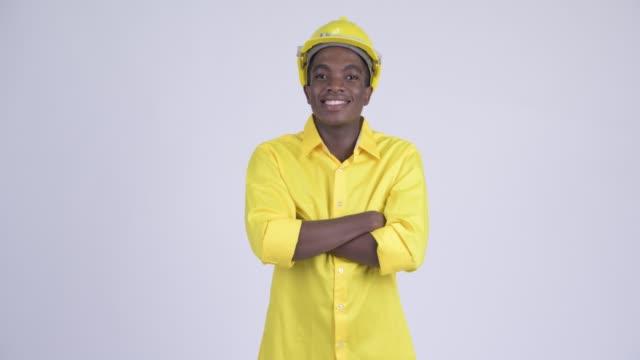 Feliz jovem empresário africano como engenheiro com os braços cruzados - vídeo