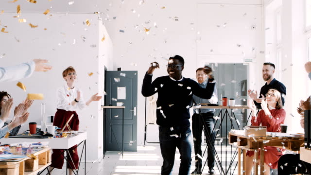 RED EPIC-W 8К Happy young African businessman celebrating success dancing with confetti and team at office slow motion.