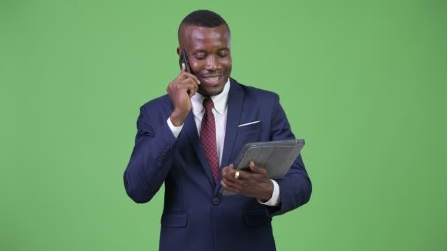 glücklicher junger afrikanischer geschäftsmann, der am telefon spricht und digitales tablet nutzt - mann bart freisteller stock-videos und b-roll-filmmaterial