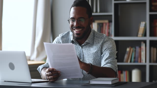 Happy young african male student feel excited read documents Happy amazed young african male student professional feel excited overjoyed read documents good news got new job receive salary rise payment taxes refund loan approval message sit at home office desk goal post stock videos & royalty-free footage