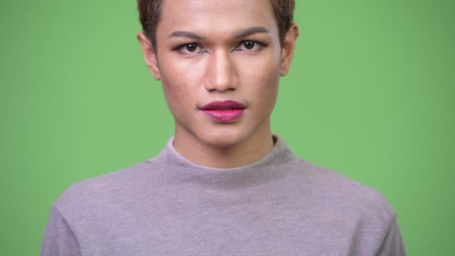 Happy young androgynous Asian man smiling Studio shot of androgynous young Asian man wearing makeup against chroma key with green background transgender stock videos & royalty-free footage