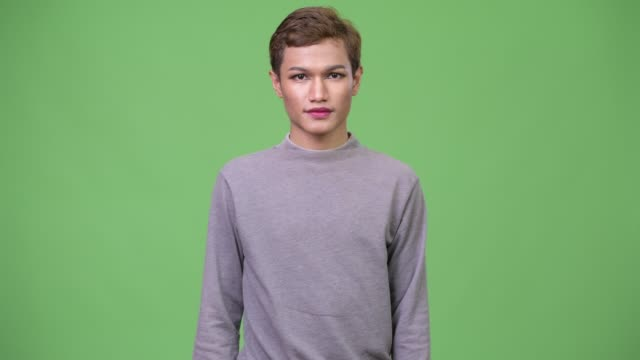 Happy young androgynous Asian man with arms crossed Studio shot of androgynous young Asian man wearing makeup against chroma key with green background transgender stock videos & royalty-free footage