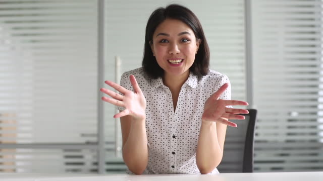 Happy young asian businesswoman talking to camera making video call