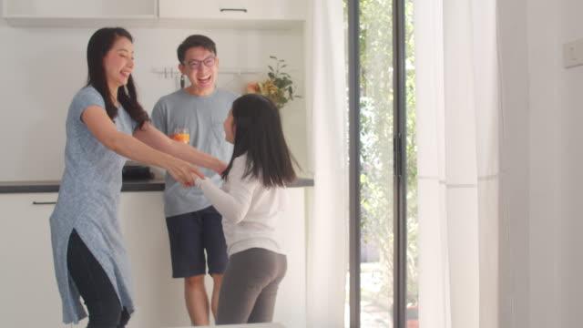 幸せな若いアジアの家族は、自宅で朝食後に音楽やダンスを聴きます。魅力的な日本の母父と子供の娘は、朝、モダンなキッチンで一緒に過ごす時間を楽しんでいます。 - 母娘 笑顔 日本人点の映像素材/bロール