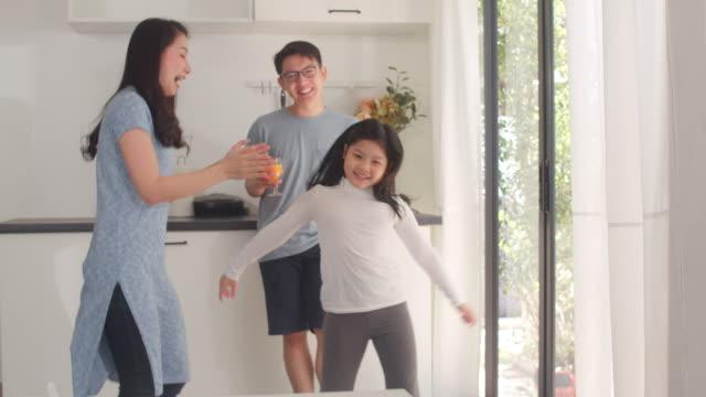 幸せな若いアジアの家族は、自宅で朝食後に音楽やダンスを聴きます。日本の母父と子供の娘は、朝、モダンなキッチンで一緒に過ごす時間を楽しんでいます。スローモーション。 - 母娘 笑顔 日本人点の映像素材/bロール