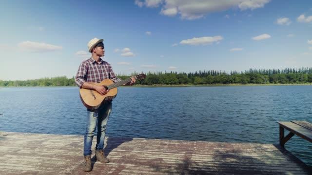 glad ung asiatisk man spela klassisk gitarr och står på lakeside och blå himmel i bakgrunden, kopia utrymme - gitarrist bildbanksvideor och videomaterial från bakom kulisserna