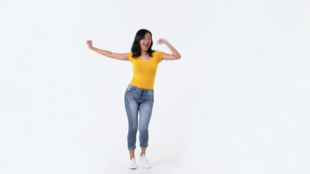 Happy young Asian woman having fun dancing Happy young Asian woman having fun smiling, dancing and looking at camera in studio against white background full length stock videos & royalty-free footage