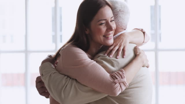 Happy young attractive woman visiting elderly senior father.
