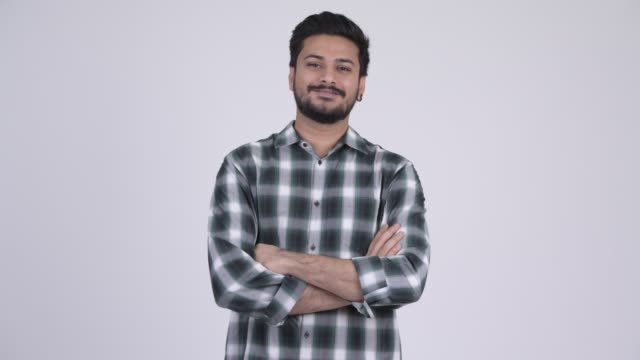 Happy young bearded Indian hipster man smiling with arms crossed