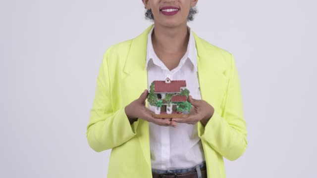 Happy young beautiful African businesswoman with house figurine