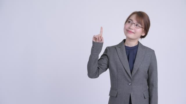 幸せな若い美しいアジアのビジネスウーマンは考え、上向き - 指差す 女性点の映像素材/bロール