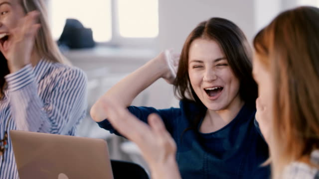 Happy young beautiful manager woman laughing, clapping and celebrating while listening to her boss at office meeting.