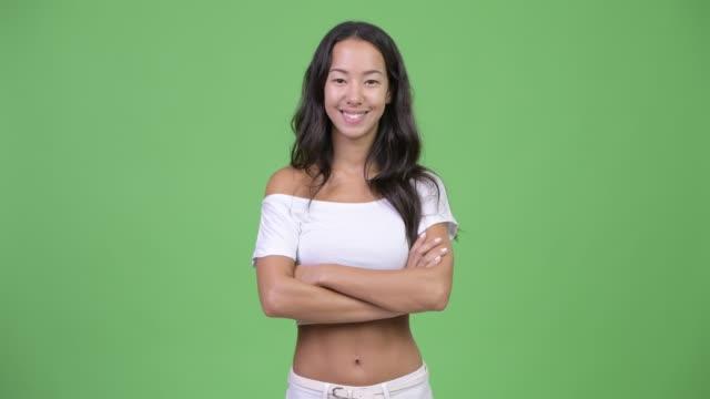 Mulher multi-étnica bonita nova feliz que sorri com os braços cruzados - vídeo