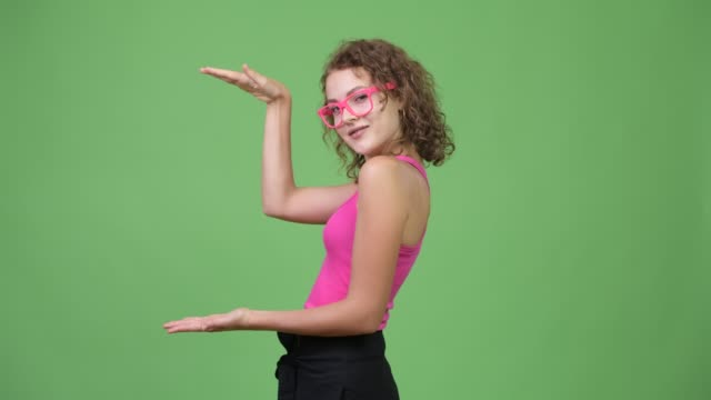 Happy young beautiful nerd woman snapping fingers and showing something Studio shot of young beautiful nerd woman with curly blond hair and blue eyes against chroma key with green background snapping stock videos & royalty-free footage