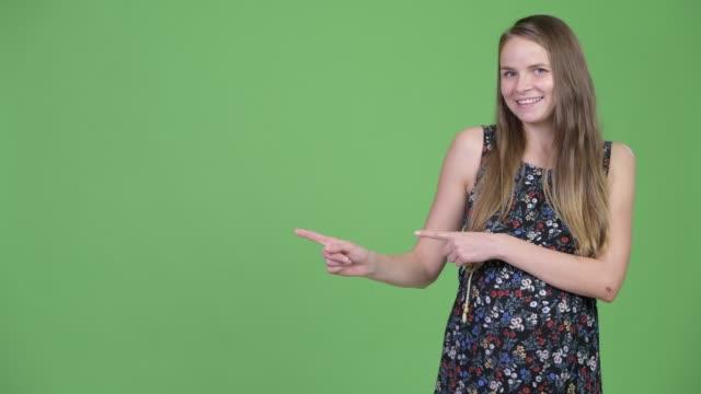 幸せな若い美しい妊婦が指を指し、何かを示しています - 指差す 女性点の映像素材/bロール