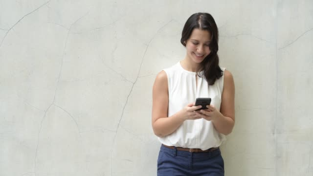 Happy Young Beautiful Woman Leaning On Wall While Using Phone Outdoors Portrait of young beautiful Eurasian brunette woman outdoors leaning stock videos & royalty-free footage