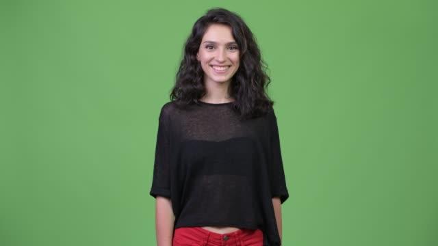 Mulher bonita nova feliz com sorriso ondulado longo do cabelo - vídeo