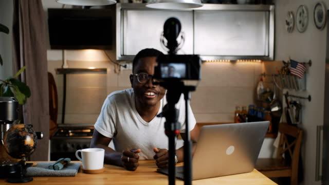 행복 한 젊은 블랙 인기 있는 소셜 미디어 블로거 남자 라이브 스트리밍 그의 온라인 블로그에 카메라를 사용 하 여 홈 슬로우 모션. - influencer 스톡 비디오 및 b-롤 화면