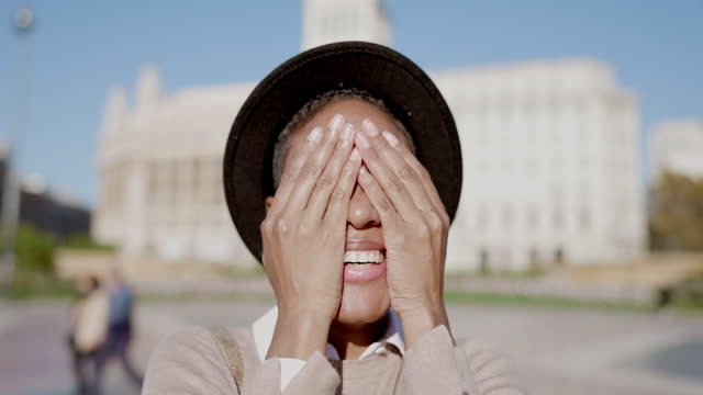 Happy young black woman covering her face with hands