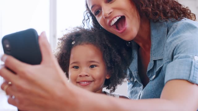 Happy young black woman taking selfie with her daughter
