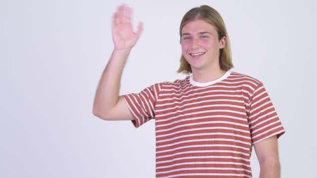 vídeos de stock e filmes b-roll de happy young blonde handsome man waving hand - cabelo comprido