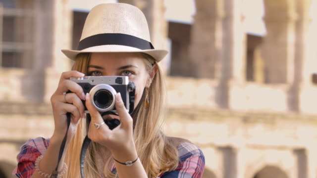Happy young blonde woman with blue eyes and long hair, taking pictures looking at camera with a vintage camera at Colosseum, Rome.