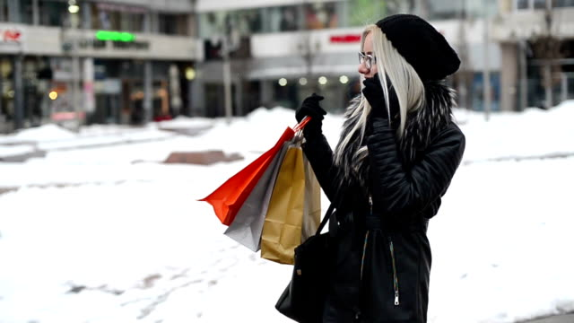 Happy young blonde woman with shopping bags in the city video