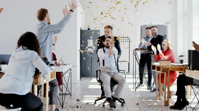 RED EPIC Happy young boss celebrates success with colleagues team and confetti at multiethnic modern office slow motion. video
