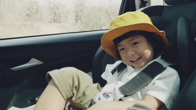 Happy young boy to travel. happy boy traveling on vacation, wearing a seatbelt in the back seat in a car. land vehicle stock videos & royalty-free footage