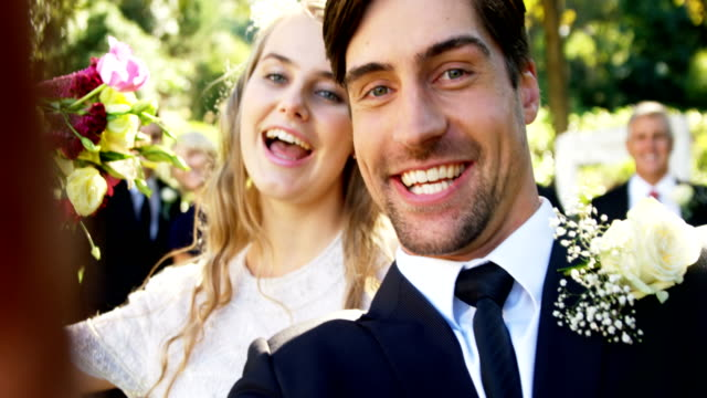 happy young bride and groom taking selfie 4k 4k - matrimonio video stock e b–roll