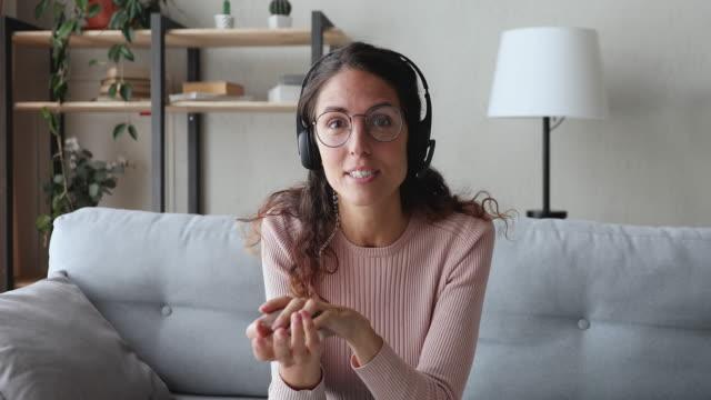 vidéos et rushes de jeune femme d'affaires heureuse utilisant le casque parlant à la caméra web - professeur(e)