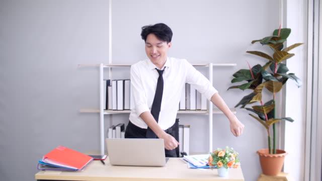 stockvideo's en b-roll-footage met gelukkige jonge zakenman bij bureau, jonge zakenman die in bureau danst - aziatische etniciteit