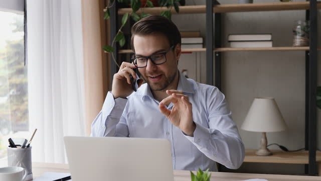 Happy young businessman in eyeglasses holding mobile phone call.