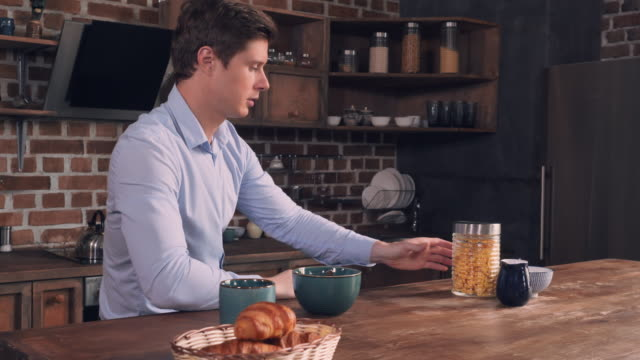 Happy young businessman in kitchen video